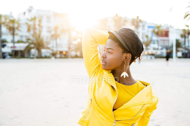 Portrait of African American woman in stylish bright jacket looking away on sandy beach blurred background — Stock Photo