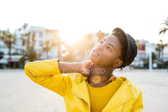 Portrait of African American woman in stylish bright jacket looking up on sandy beach blurred background — Stock Photo