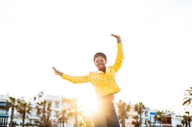 Heureuse femme afro-américaine en veste lumineuse élégante sautant avec les mains vers le haut sur fond blanc — Photo de stock