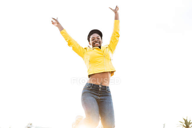 Low angle of happy African American woman in stylish bright jacket jumping with hands up on white background — Stock Photo