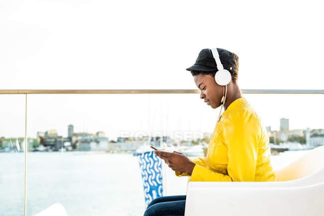 Вид сбоку афроамериканки в стильной яркой куртке, использующей мобильный телефон и слушающей музыку в наушниках — стоковое фото