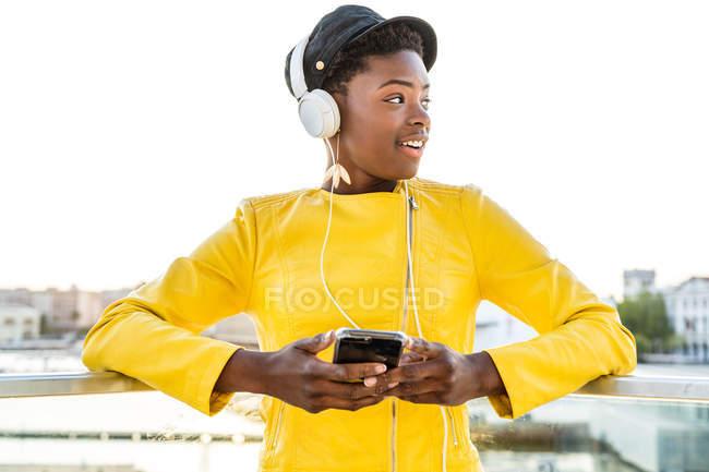 Афроамериканець жінка в стильному яскравому піджаку за допомогою мобільного телефону і прослуховування музики на навушниках — стокове фото