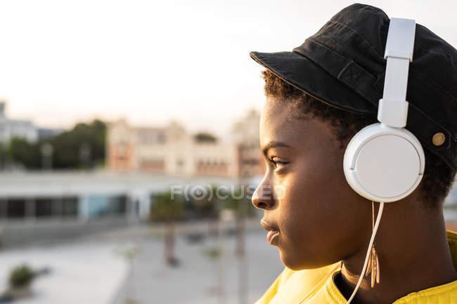 Vista lateral da mulher afro-americana em fones de ouvido apoiados na varanda de vidro e olhando para o fundo embaçado — Fotografia de Stock