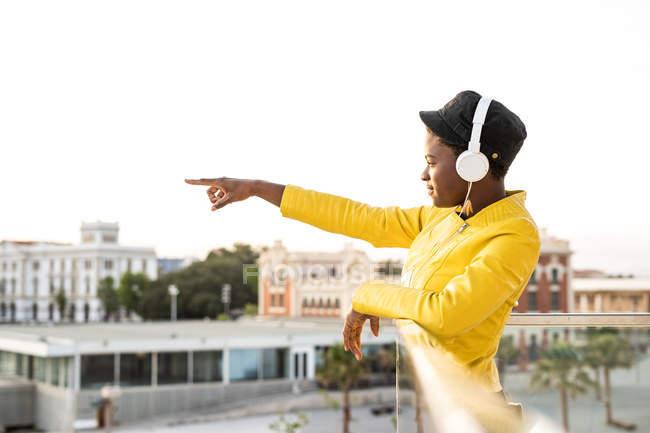 Seitenansicht der afroamerikanischen Frau in trendiger Jacke, die wegschaut und mit dem Finger auf verschwommenen Hintergrund zeigt — Stockfoto