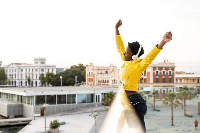 Seitenansicht einer afrikanisch-amerikanischen Frau in trendiger Jacke, die mit den Armen nach oben auf verschwommenem Hintergrund blickt — Stockfoto