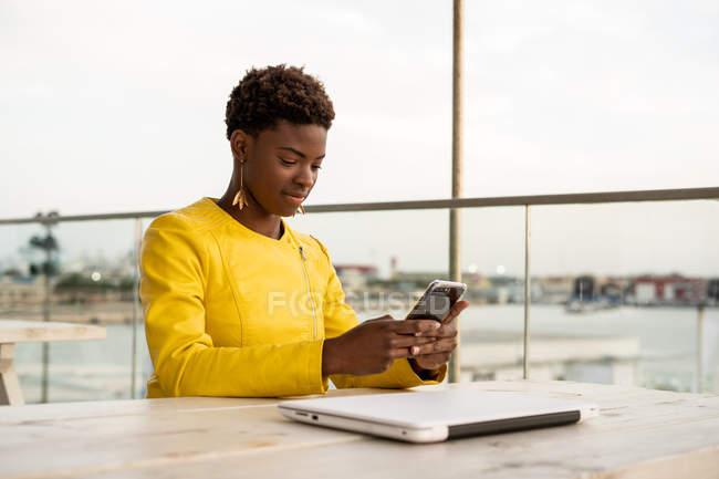 Teléfono inteligente de mensajería femenina afroamericana concentrada mientras se relaja en la mesa de madera - foto de stock