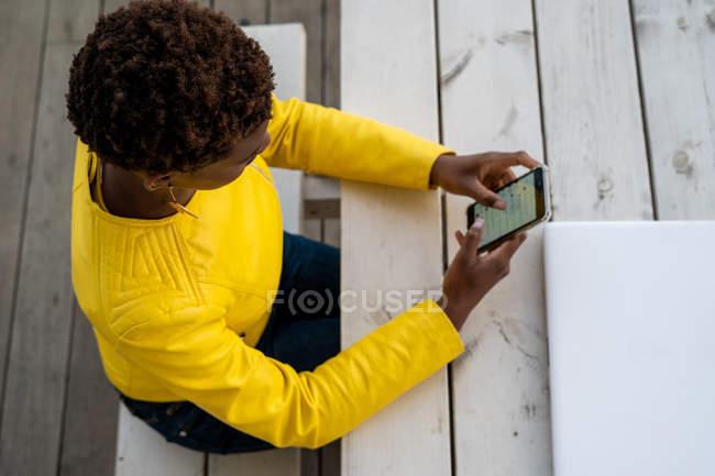 Desde arriba de la mensajería femenina afroamericana concentrada con teléfono inteligente mientras se relaja en la mesa de madera - foto de stock