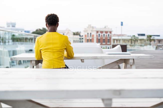 Opinião traseira a fêmea concentrada do americano africano que senta-se e que relaxa na tabela de madeira — Fotografia de Stock