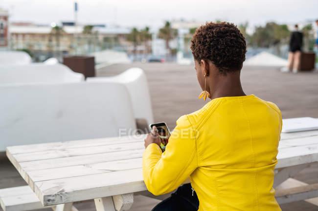 Vista posterior de la mensajería femenina afroamericana concentrada con teléfono inteligente mientras se relaja en la mesa de madera - foto de stock