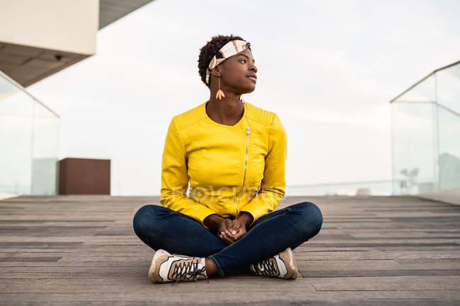 Стильна афроамериканець жінка в сучасній куртці розслабляючий сидячи на дерев'яній підлозі і оглядаючись — стокове фото
