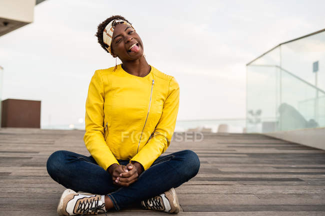 Stylish African American female in modern jacket relaxing sitting on wooden floor and looking in camera making silly faces — Stock Photo