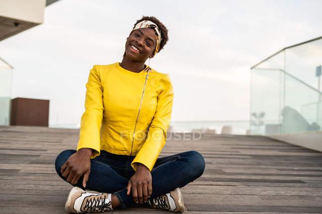 Elegante mujer afroamericana en chaqueta moderna relajante sentado en el suelo de madera y mirando en la cámara sonriendo - foto de stock