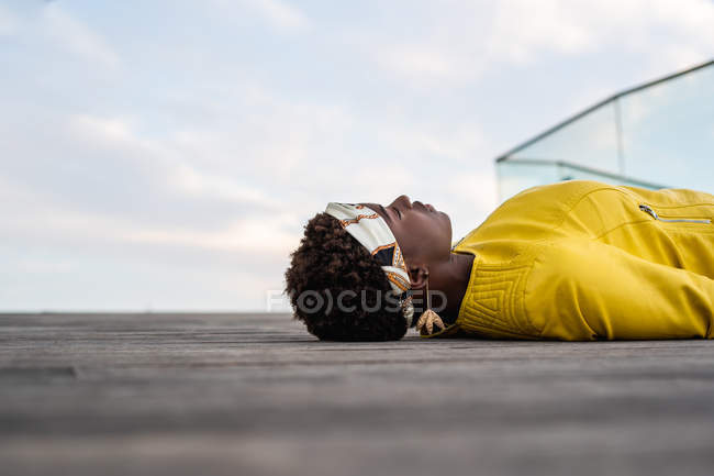 Side view of stylish African American female in modern jacket relaxing on wooden floor and looking away — Stock Photo