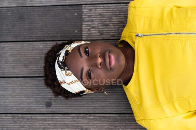 Dall'alto elegante donna afroamericana in giacca moderna rilassante sul pavimento in legno e guardando in macchina fotografica — Foto stock
