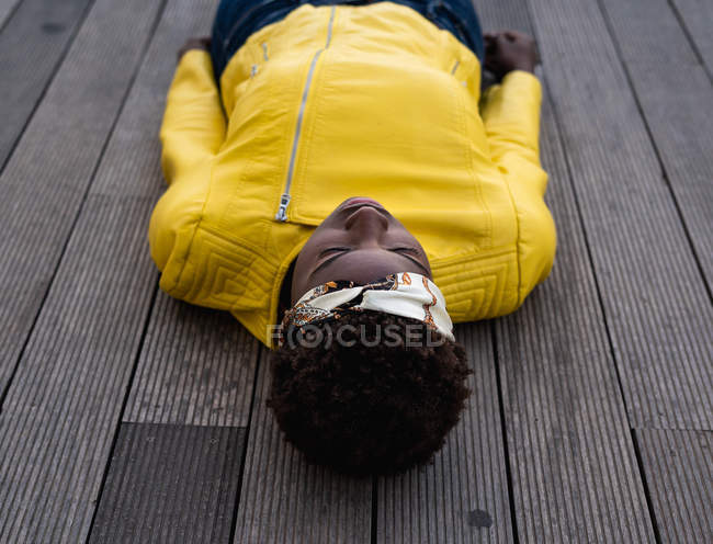 From above stylish African American female in modern jacket relaxing on wooden floor and looking away — Stock Photo