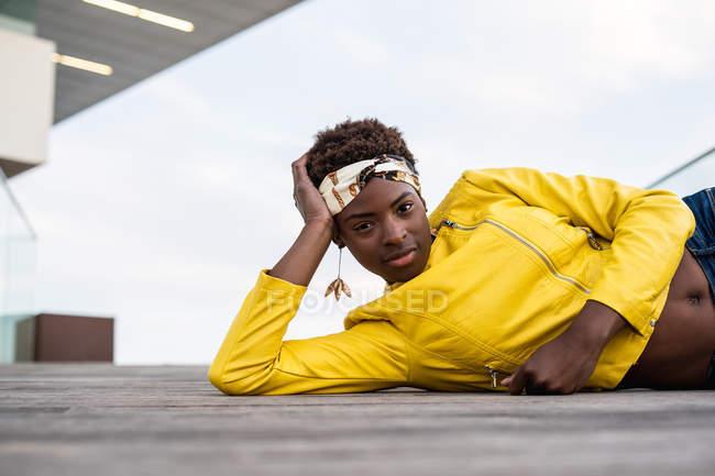 Elegante donna afroamericana in giacca moderna rilassante sdraiata sul pavimento in legno e guardando nella fotocamera — Foto stock