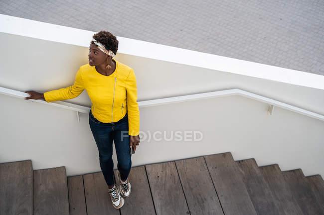 Vista de ángulo alto de la mujer afroamericana alegre en elegante desgaste escalofriante en las escaleras y mirando hacia otro lado - foto de stock