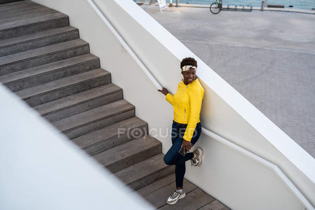 Vista ad alto angolo di donna afro-americana felice in elegante usura agghiacciante sulle scale e guardando altrove — Foto stock