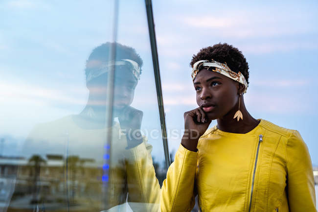 Side view of serene African American woman chilling on glass balcony and looking away — Stock Photo