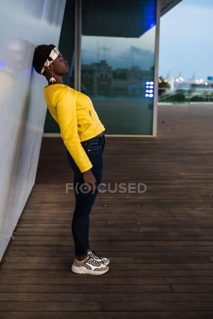 Vista laterale della moderna donna afroamericana appoggiata al muro di un edificio moderno e sognare ad occhi aperti in città al tramonto guardando altrove — Foto stock