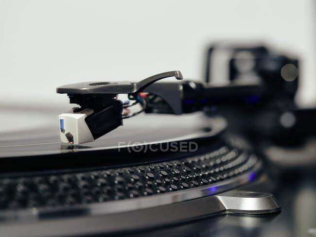 Nahaufnahme der Oberseite eines alten schwarzen Plattenspielers mit Tonarm, der die Position der Kassettenabtastrinne beibehält und Schallplatte abspielt — Stockfoto