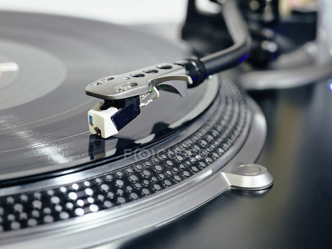 Closeup of top of old black turntable with tonearm maintaining position of cartridge tracing groove and playing LP record — Stock Photo