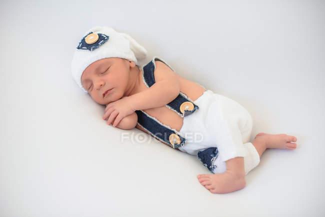 Adorabile neonato in cappello e pantaloni che dorme tranquillamente su un morbido materasso bianco a casa — Foto stock