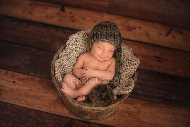 Nudo neonato in maglia cappello dormire in secchio sul pavimento in legno a casa — Foto stock