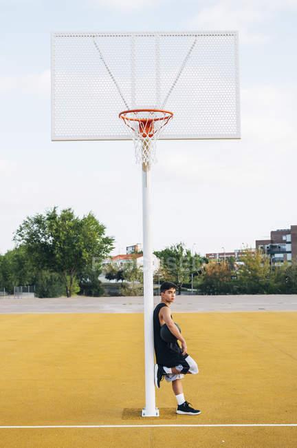 Молодой человек опирается на столб на баскетбольной площадке на открытом воздухе . — стоковое фото
