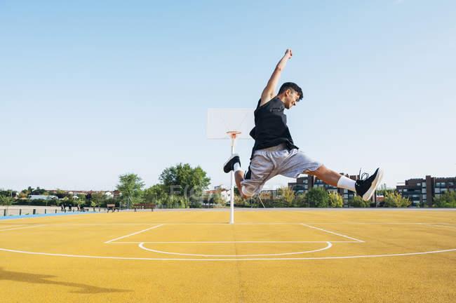 Молодой человек прыгает с черным мячом на баскетбольной площадке под открытым небом . — стоковое фото