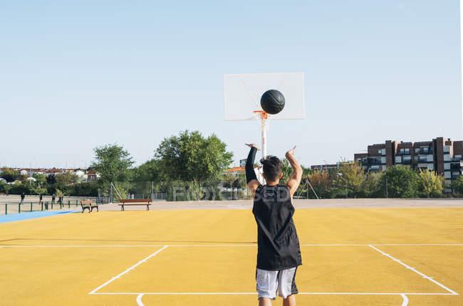 Молодой человек бросает черный мяч на желтую баскетбольную площадку на открытом воздухе с заднего вида . — стоковое фото