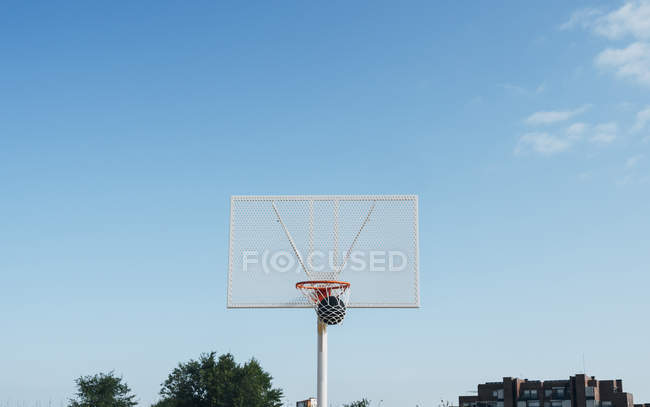 Ball into net basket in outdoor basketball court. — Stock Photo