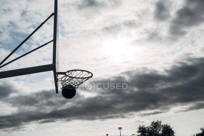 Мяч в корзину на открытой баскетбольной площадке против облачного неба . — стоковое фото