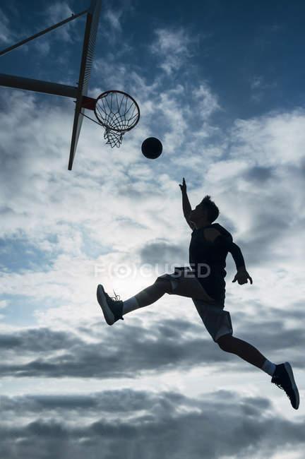 Jovem saltando para marcar na quadra de basquete ao ar livre contra o céu nublado . — Fotografia de Stock