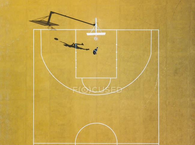 Vista aérea do homem jogando basquete na quadra amarela ao ar livre . — Fotografia de Stock
