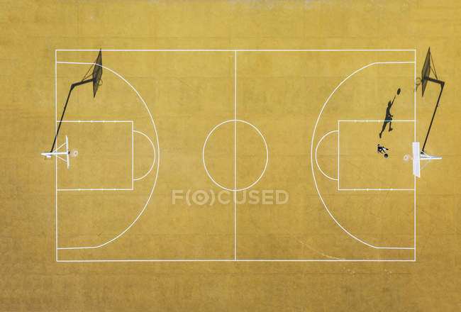 Aerial view of man playing basketball on yellow outdoor court. — Stock Photo