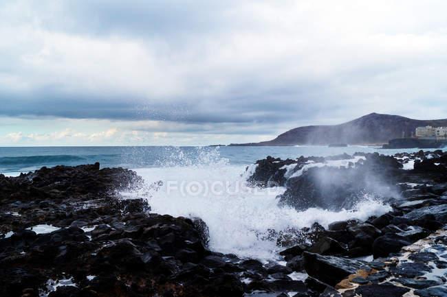 Голубые волны океана с белой пенной текстурой на фоне скал — стоковое фото