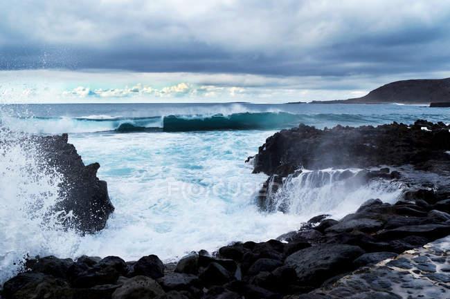 Onde blu dell'oceano con texture in schiuma bianca contro le rocce — Foto stock