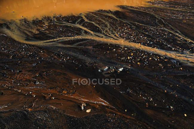 Du haut d'un sol sombre abstrait avec une flaque d'eau sale et un écoulement d'eau rouillée — Photo de stock