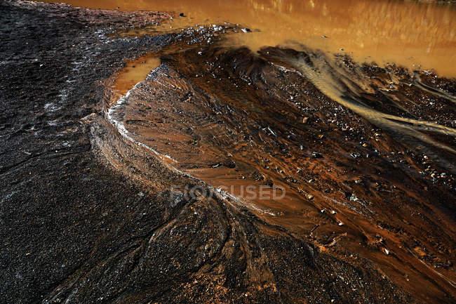 De cima do solo escuro abstrato com poça suja e gotejamento de água enferrujada flui — Fotografia de Stock