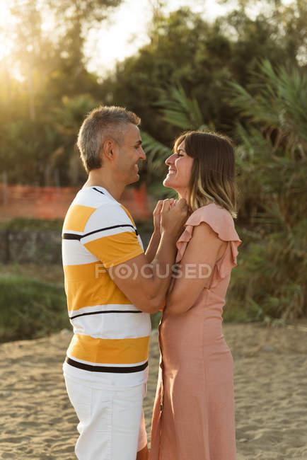 Seitenansicht von Mann und Frau, die sich Händchen halten und einander mit glücklichem Lächeln im Freien betrachten — Stockfoto