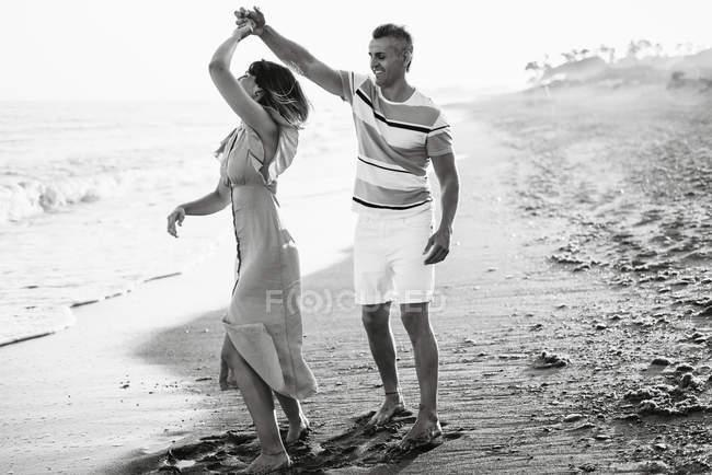 Доросла людина посміхається і крутиться жінка в танці, розважаючись на піщаному пляжі біля моря. — стокове фото