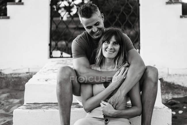 Черно-белый веселый взрослый мужчина и женщина улыбаются и обнимаются, сидя на ступеньках снаружи здания — стоковое фото