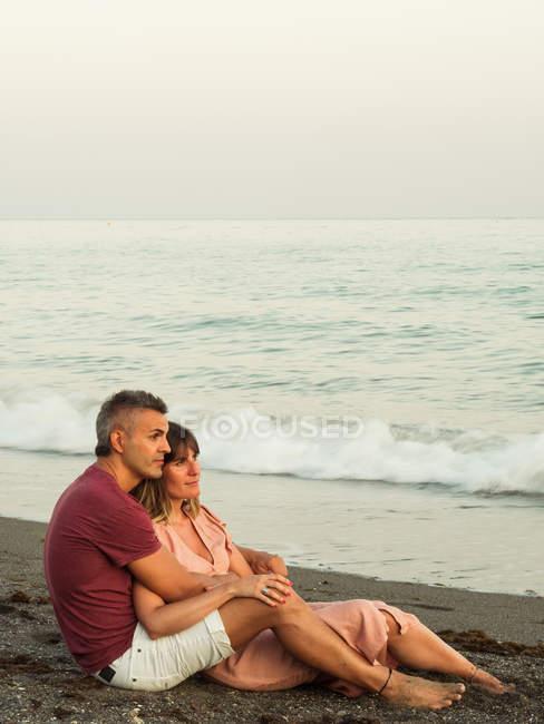 Взрослый мужчина и женщина в полной длине улыбаются и обнимаются, сидя на песке возле моря и расслабляясь во время свидания — стоковое фото