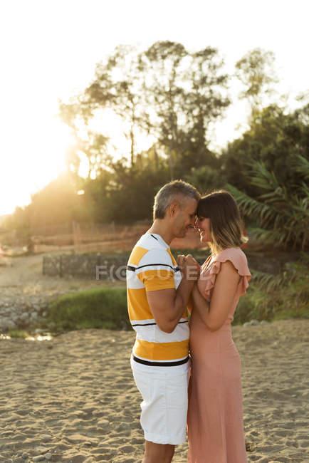 Seitenansicht eines erwachsenen Mannes und einer erwachsenen Frau, die sich Händchen halten und einander mit glücklichem Lächeln im Freien betrachten — Stockfoto