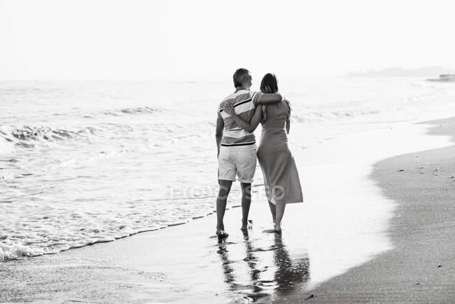 Vista trasera del hombre descalzo y la mujer abrazando mientras camina en la playa de arena hacia el mar ondulante en el complejo - foto de stock