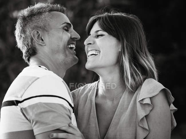 Paar sieht einander mit glücklichem Lächeln und Lachen an — Stockfoto