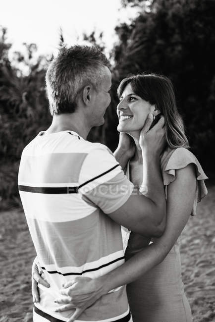 Couple looking at each other with happy smile on sandy beach — Stock Photo