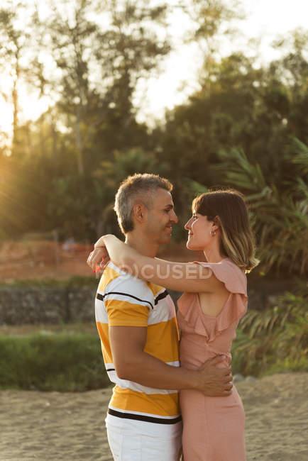 Paar schaut einander mit glücklichem Lächeln im Gegenlicht an — Stockfoto