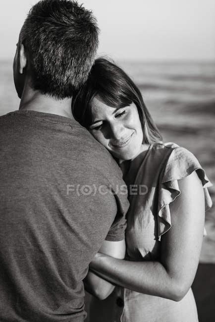 Взрослая женщина, опирающаяся на мужчину, стоя на пляже рядом с морем — стоковое фото